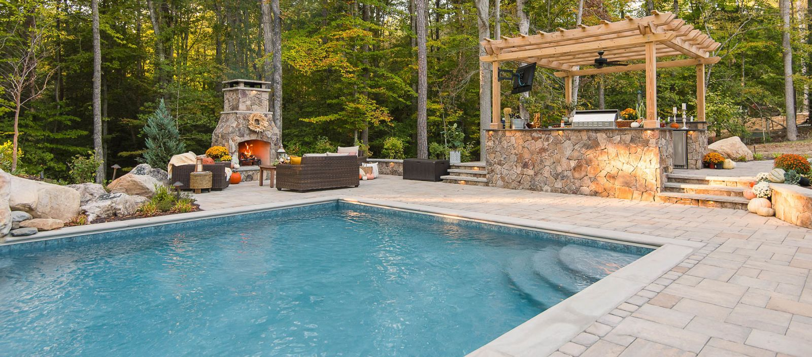 Backyard hardscape project with fireplace, pool and kitchen