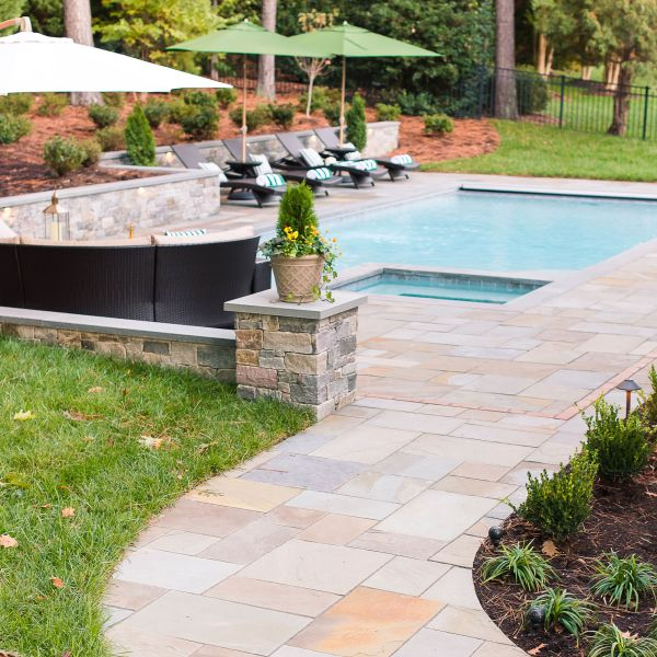 Stone path leading to a backyard pool with retaining wall features