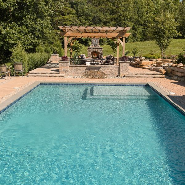 Large backyard pool surrounded with stone pavers, natural stone walls and steps, a waterfall wall feature
