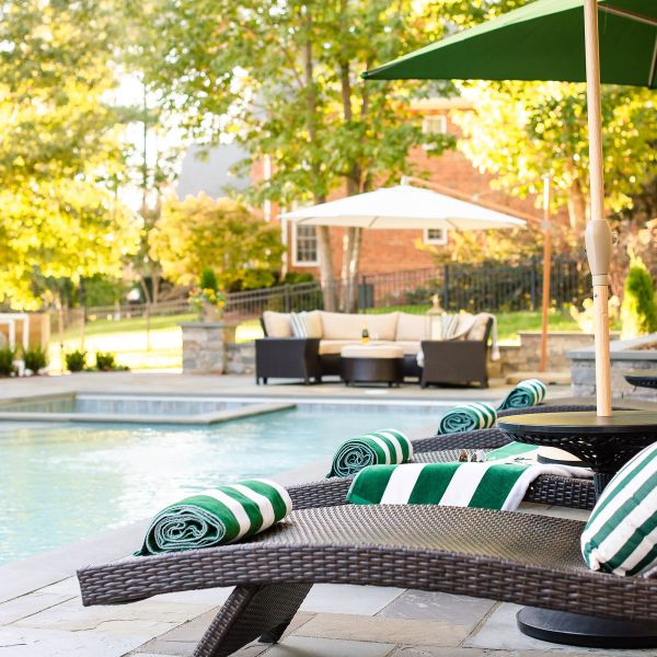 Green striped towels rolled up on lounge chairs by the pool