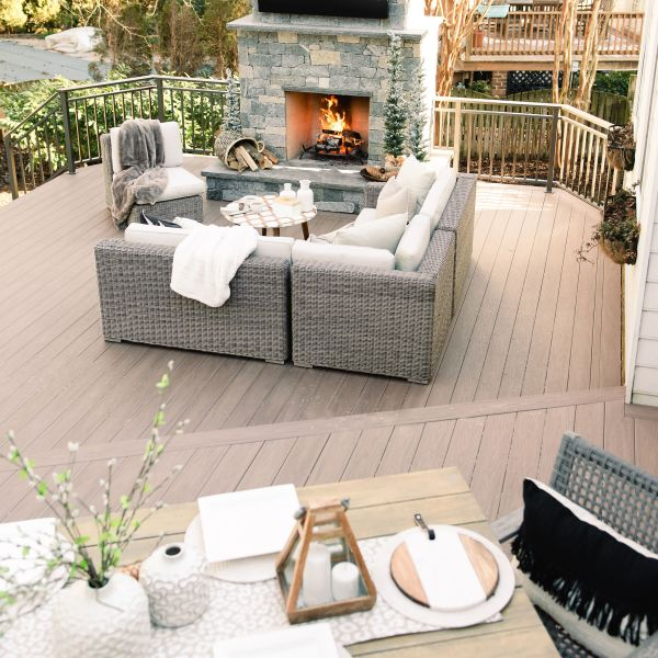 two tiered composite back deck with stone fireplace and furniture