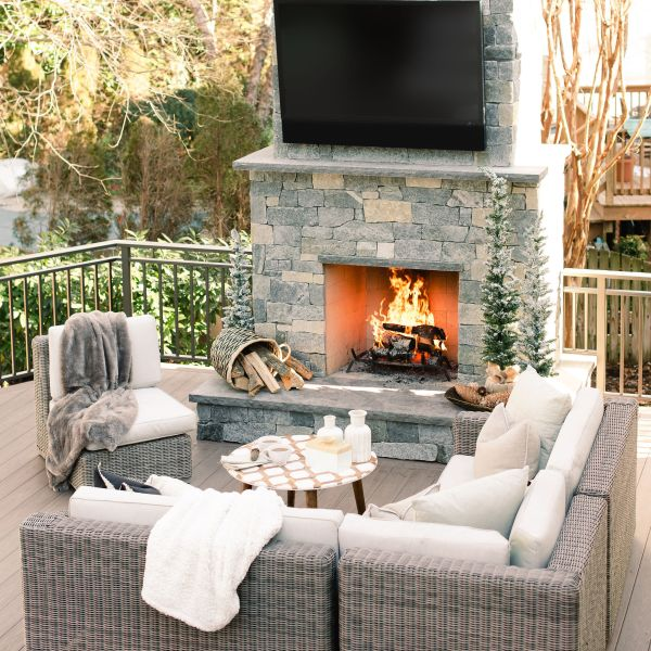 Furnished back deck in front of an outdoor fireplace and TV