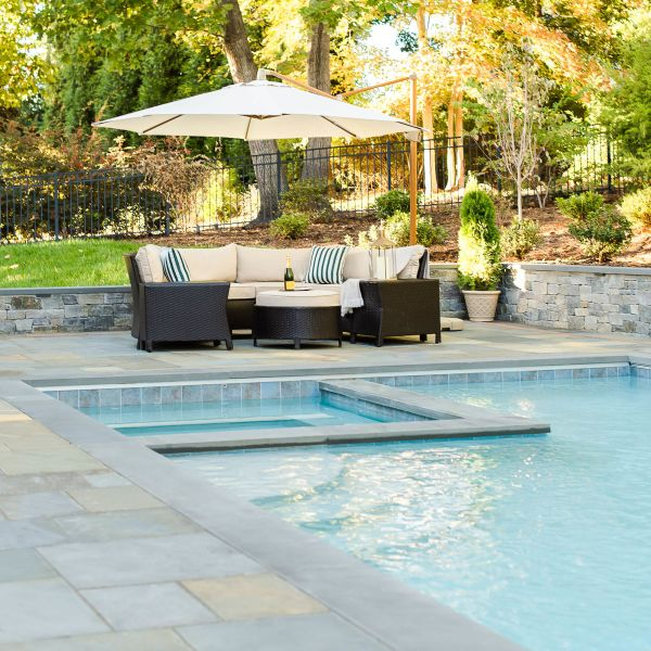 outdoor lounge area features wicker seats and off-white cushions under a large umbrella near an underground pool