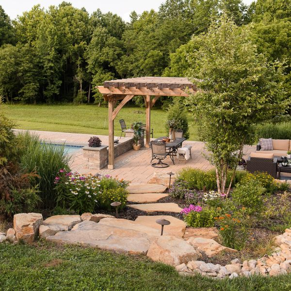 Paver patio with pergola, gunite pool, and native landscaping