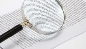 Magnifying glass and a stack of paper