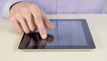 man-using-apple-ipad-tablet-with-finger-on-touchscreen-on-desk-o-640×427