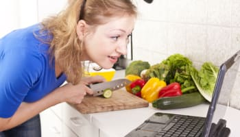 cooking-with-laptop-computer-in-kitchen-whilst-chopping-with-knife-o