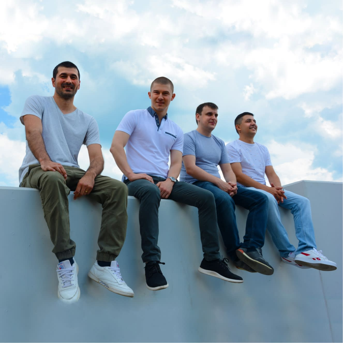 Senior team sitting on top of a wall