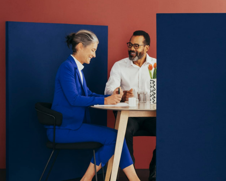Une femme et un homme qui collaborent dans une salle de réunion moderne, confortable, privée conçue par Breather.