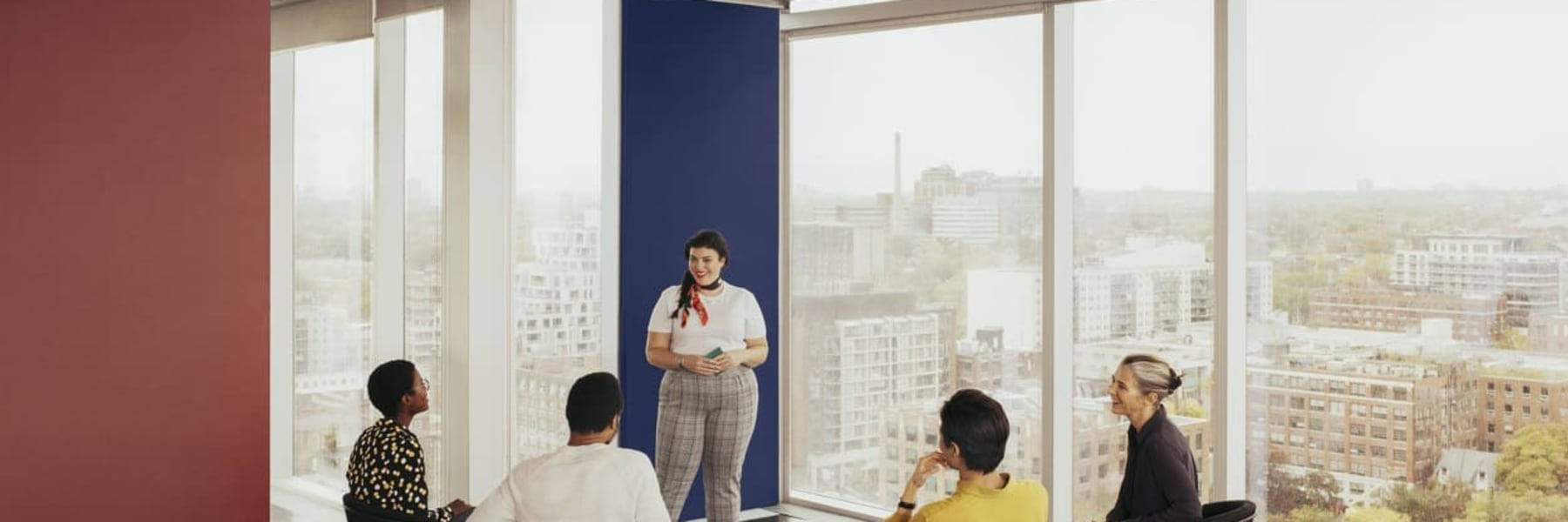 A woman standing in front of her colleagues sitting in a semi-circle makes a presentation in a Breather space with a great view of the city