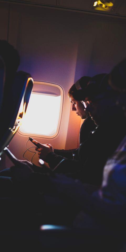 Jongeman gebruikt telefoon in vliegtuig (portrait)