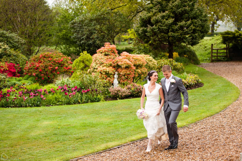 happy newlyweds stroll around moorland garden hotel, a rustic wedding venue in the uk