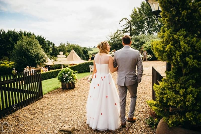 Married couple walk around Lodge Farm House, an outdoor wedding venue in Hertfordshire