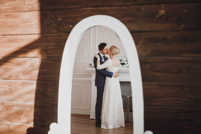 Bridebook.co.uk Couple kissing in reflection of dresser mirror