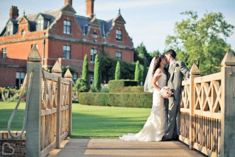 a couple kiss on a wooden bridge outside Chippenham Park wedding venue, in Cambridgeshire