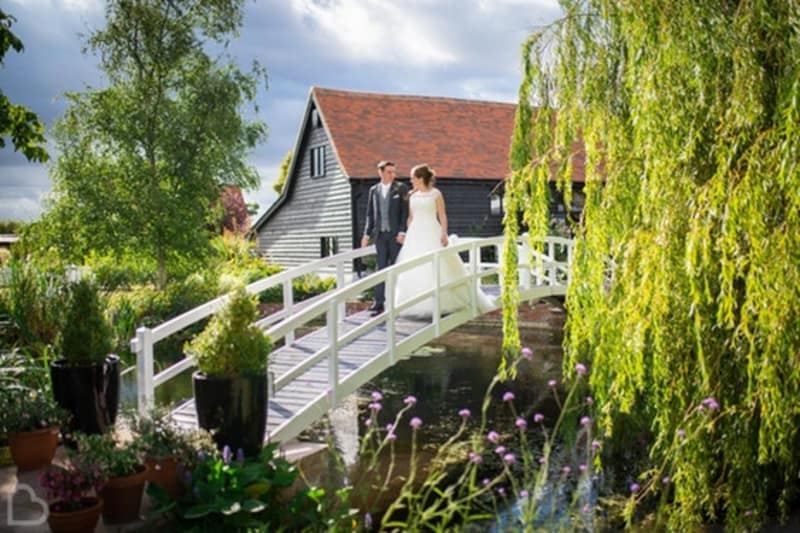The High House wedding venue, a married couple walk over a small white bridge in Essex