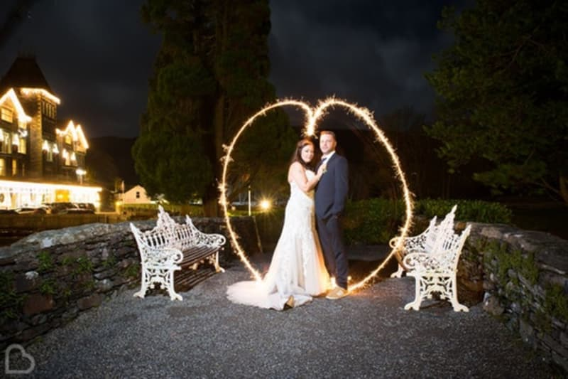 Married couple pose outside The Lodore Falls Hotel a wedding venue in Cumbria