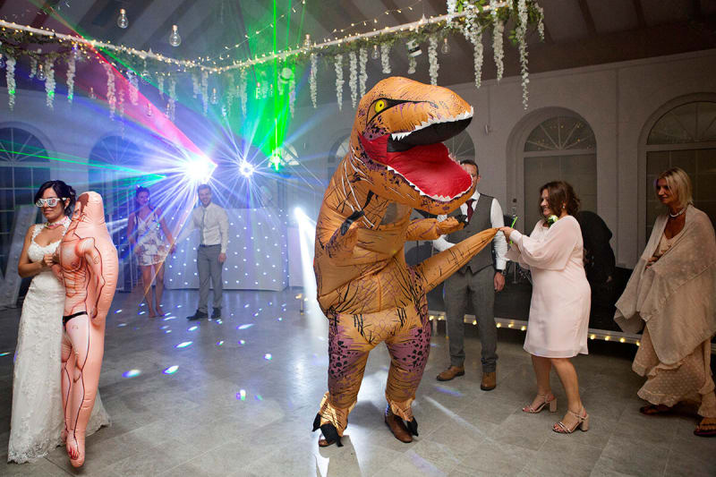 guest in t-rex costume dances at wedding