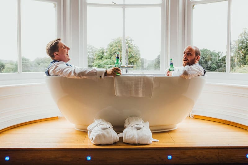 two groomsmen lauging in an empty bathtub and having a beer, best wedding photos of 2018