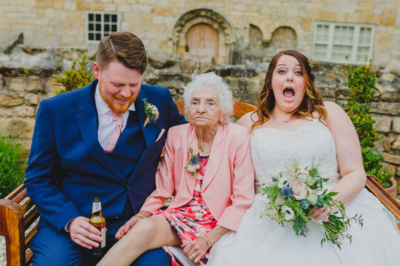 bride groom and grandma pose for a wedding photo