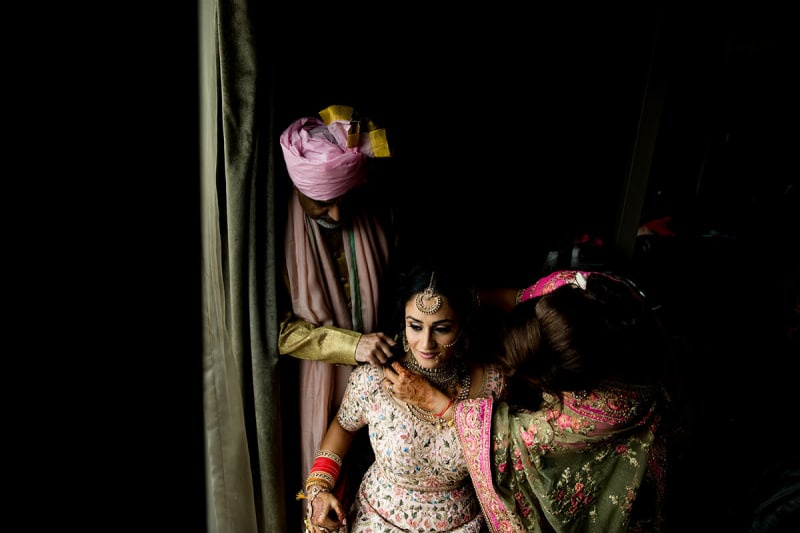 indial wedding parents helping the bride get ready