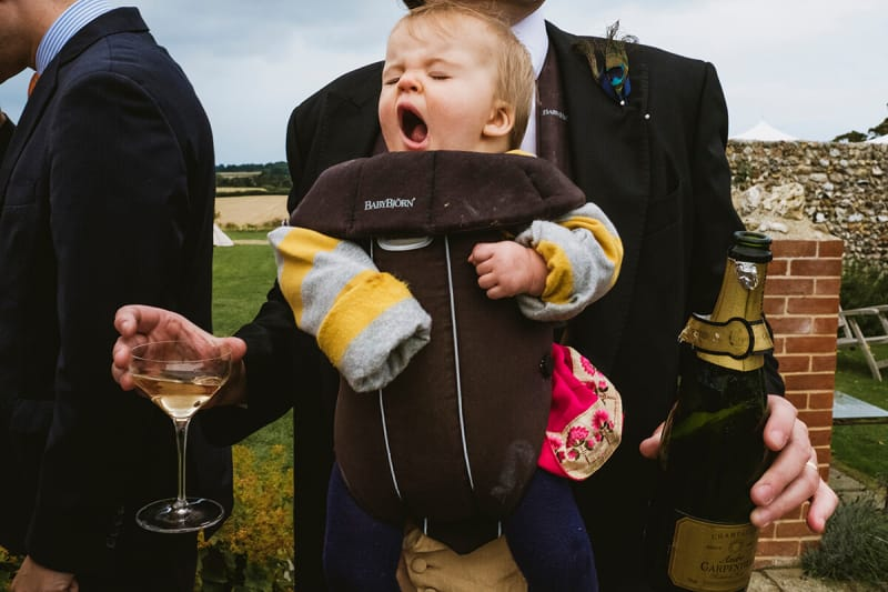 dad carries his baby at a wedding as he has a glass of champagne