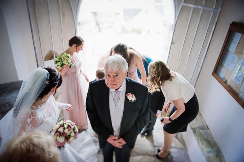 bride's dad looking up at camera during her wedding