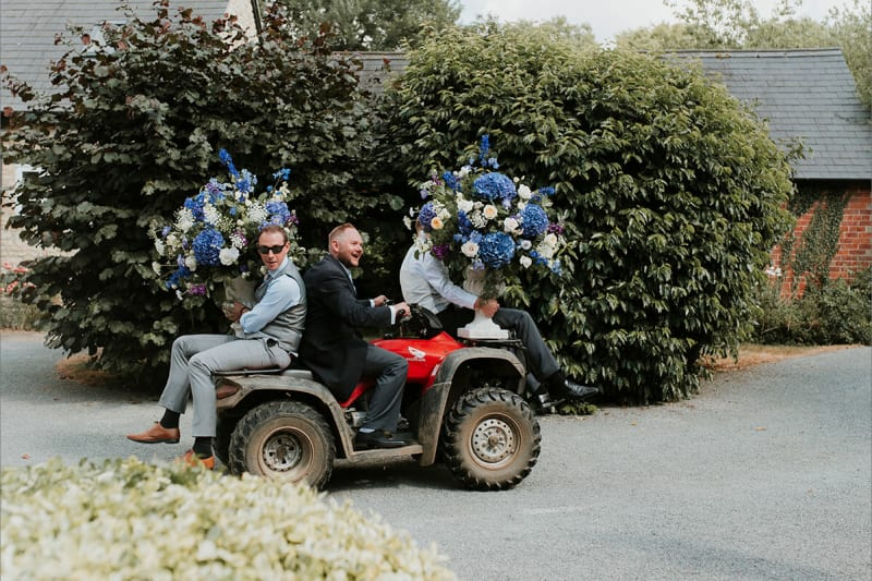 groomsmen carrying flowers on a truck