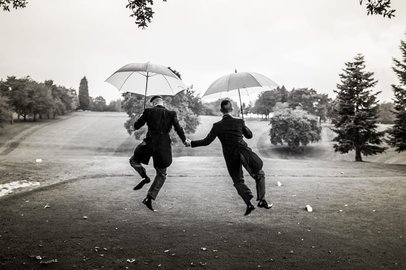 two grooms dancing with umbrellas on their wedding day