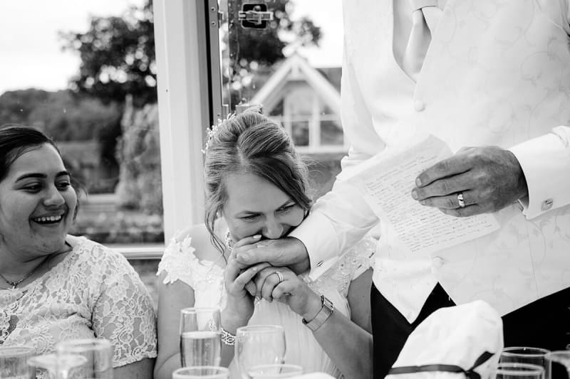 bride holds her dad's hand as he makes wedding speech