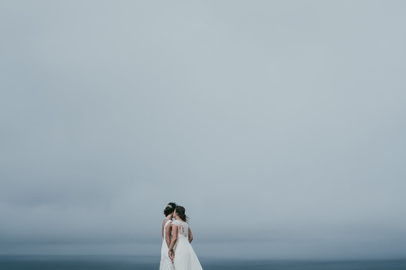 two brides kiss under cloudy skies