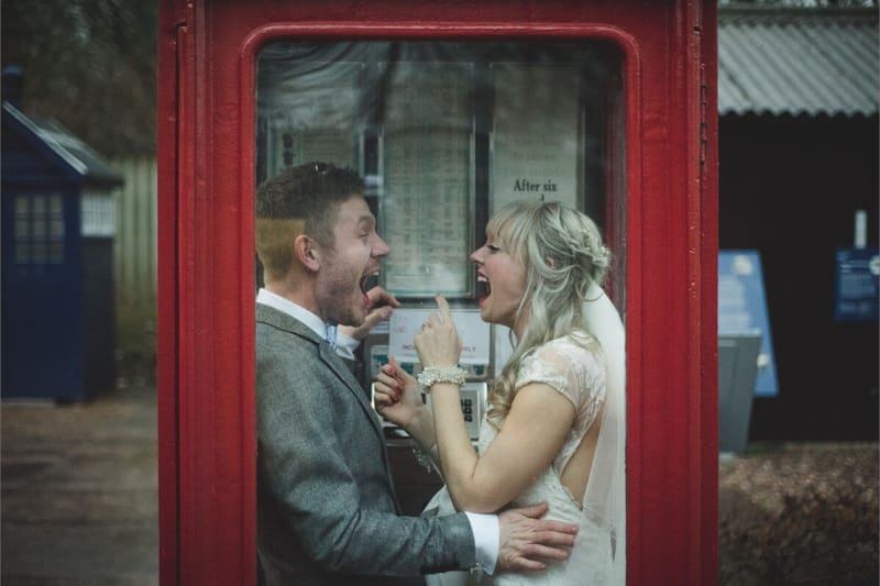 a married couple laughing in an old phone booth