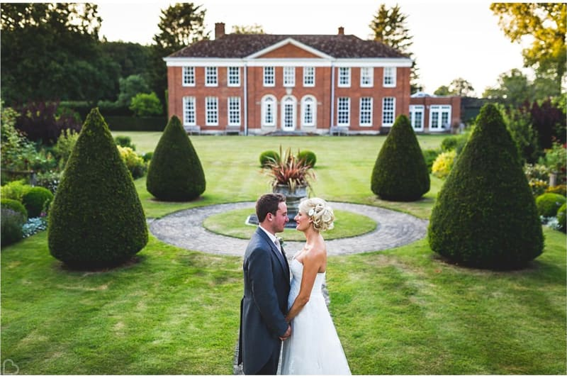 newlyweds pose in front of hockering house a country wedding venue in the uk