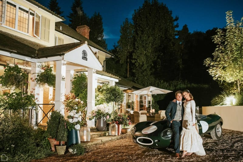 a couple poses with their sports car outside russets country house wedding venue
