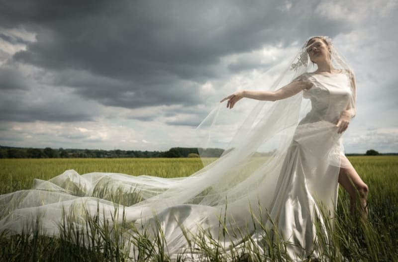 Bride walking in field wearing re-use wedding dress