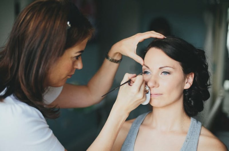 Make up artist putting sustainable make up on bride to be on wedding day