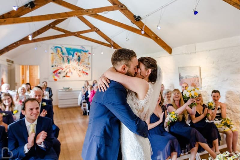 A newly married couple kisses in Monks Withecombe, a barn wedding venue in Devon