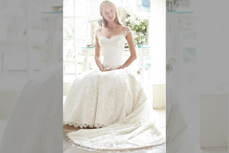 Phillipa Lepley wedding dress on model sitting with hands in lap