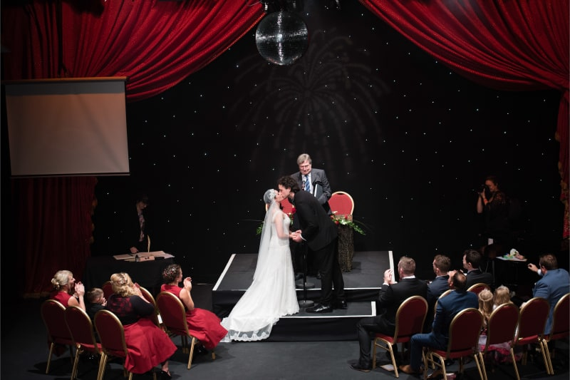 Bridebook.co.uk bride and groom kiss on stage