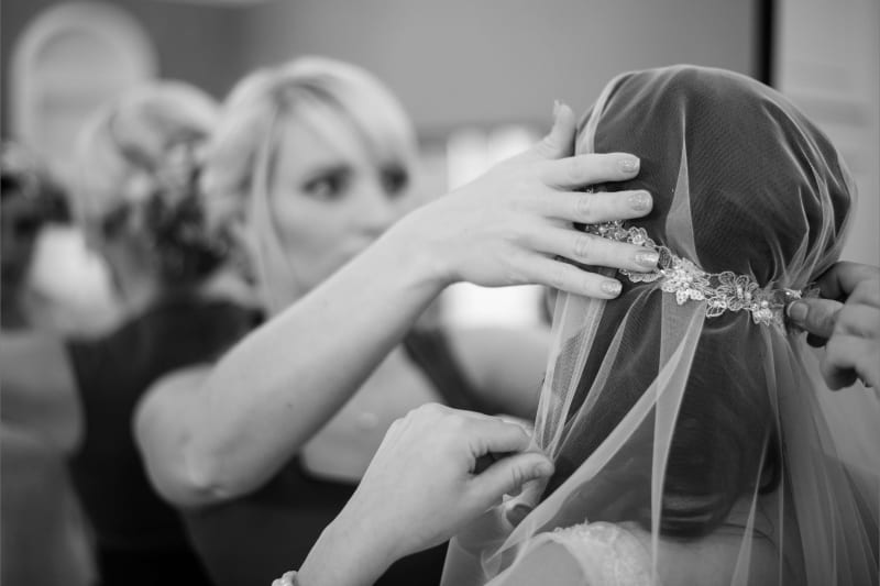 Bridebook.co.uk bride putting on cap veil