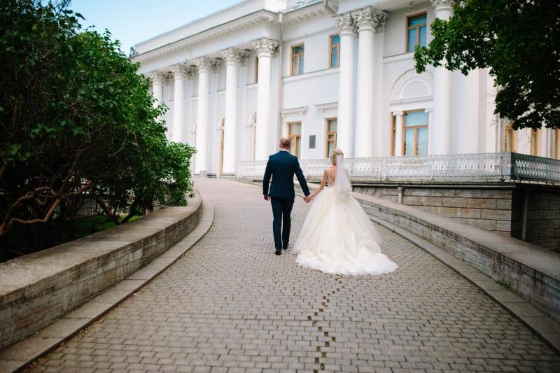 Bridebook.co.uk Bride and groom walking down drive