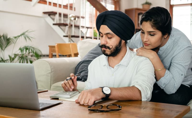 Engaged couple at home looking at saving money by browsing wedding venue virtual tours at home