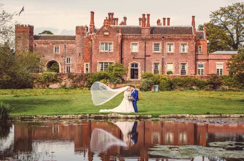 Married couple standing in front of Hodsock Priory wedding venue in Nottinghamshire, UK