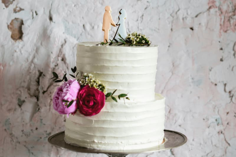 two-tier wedding cake with bride and groom cookies and flowers