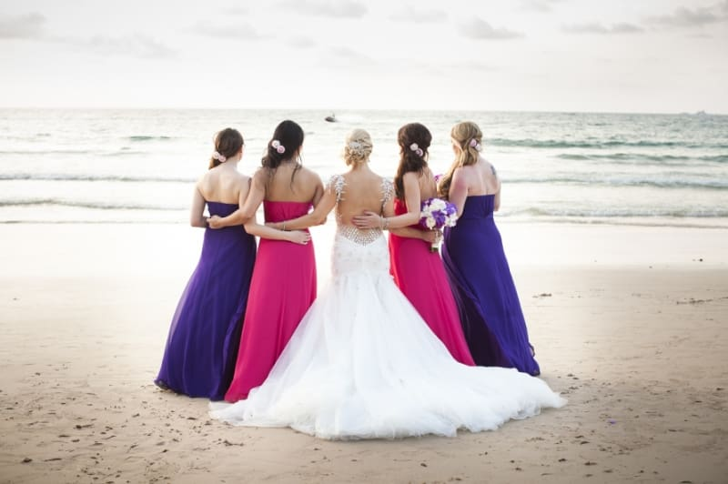 Bridebook.co.uk- bride and bridesmaids against the sea