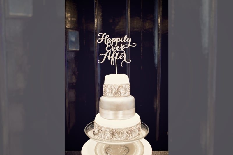 Bridebook.co.uk- white cake with metallic accents and a happily ever after topper