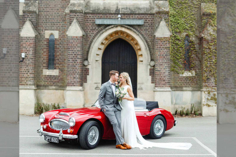 Bridebook.co.uk- bride and groom smiling next to red wedding car