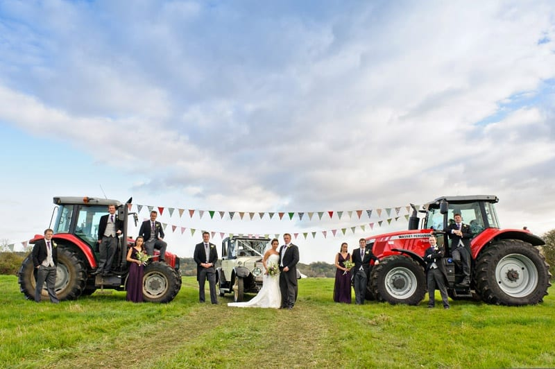 Bridebook.co.uk- bride groom and wedding party next to tractors