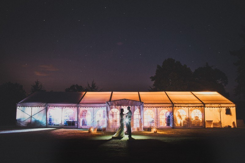 Bridebook.co.uk- bride and groom kiss against marquee in the night