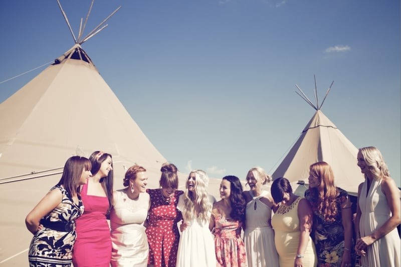 Bridebook.co.uk- bride and friends outside marquee